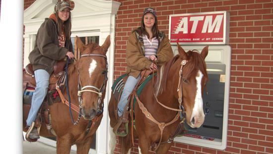 Two young ladies on horseback in front of ATM mach